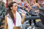 Woman drinking water beside treadmill — Stock Photo