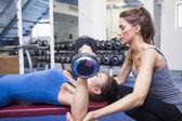Treinador feminino, ajudando o cliente a levantar pesos — Foto Stock