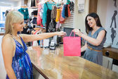 Woman handing over shopping bag at cash register — Stock Photo
