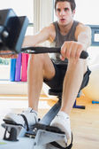 Man rowing at the row machine — Stock Photo