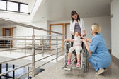Nurse talking with child in wheelchair and neck brace with mothe — Stock Photo