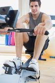 Man working out on row machine — Stock Photo