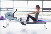 Woman working out on row machine — Foto de Stock