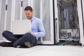 Man sitting on floor with laptop beside servers — Foto de Stock