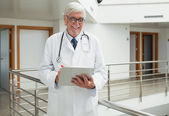 Doctor smiling as looks at patient file — Stock Photo