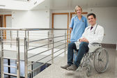 Nurse standing with doctor sitting in wheelchair — Stock Photo