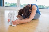 Woman in seated forward bend yoga pose — Stock Photo
