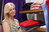 Woman stacking shelf in clothing store — Stock Photo