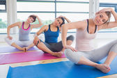 Women sitting and stretching at yoga class — Stock Photo