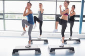 Four women raising their legs while doing aerobics — Stock Photo