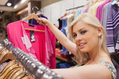 Woman is standing at a clothes rack and looking at clothes — Stock Photo