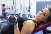 Smiling woman lifting weights — Stok fotoğraf