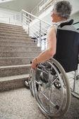 Oudere dame in rolstoel op zoek trap — Stockfoto