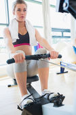 Young woman on the row machine — Stock Photo