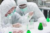绿色液体进行试验的两位化学家 — 图库照片