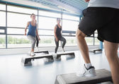 Trainer stepping with aerobic class — Stock Photo