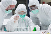 Chemist adding green liquid to test tubes with two other chemist — 图库照片