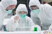 Chimiste, ajouter du liquide vert pour tubes à essai avec deux autre chimiste — Photo
