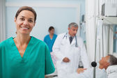 Smiling nurse standing in a hospital room — Stock Photo