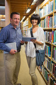 Man holding book standing next to woman using tablet pc — Stock Photo