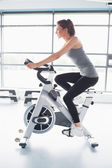 Woman energetically riding exercise bike — Stok fotoğraf