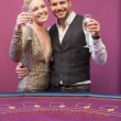 Two people toasting in a casino - Stock Photo