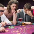 Mlosing at poker table with womcomforting him — Stock Photo #23086548