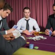 Men playing high stakes poker game - Stock Photo