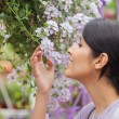 Womsmelling while holding flower — Stock Photo #23086610