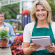 Smiling woman holding notepad with customer holding plant — Stock Photo