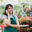 Florist doing a phone call while smiling - Stock Photo