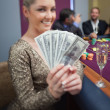 Stock Photo: Blonde fanning dollars at roulette table