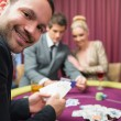 Man smiling while sitting at poker table — Stock Photo