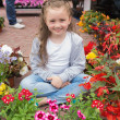 Little girl sitting on path surrounded by flowers — Stock Photo