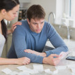Couple calculating bills in kitchen — Stock Photo #23087436