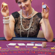 Womholding chips in her hand in casino — Stock Photo #23087526