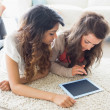 Two women looking at tablet pc on floor — Stock fotografie