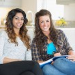 Stock Photo: Two smiling girls sitting on couch while writing on notepad