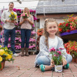 Family holding flower pots in garden center — ストック写真