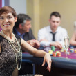 Smiling woman taking break from roulette with champagne — Stock Photo #23088006
