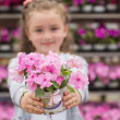 Stock Photo: Little girl with flowers in garden center