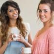Happy women holding coffee cups — Stock Photo