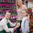 Employee giving flower pot to little girl with mother — Stock Photo #23088186