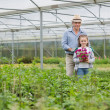 Gardener and grandchild holding a flower - Stock Photo