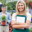 Woman holding a notepad with customer holding potted plant — Stock Photo #23088248