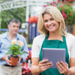 Cheerful florist holding a tablet pc in garden center — Stock Photo