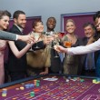 Standing clinking glasses at roulette table — Stock Photo