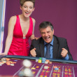 Man and woman cheering at roulette table - ストック写真