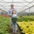 Gardener and little girl holding a watering can - ストック写真