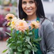 Employee smiling and holding a flower in garden center — Stock Photo
